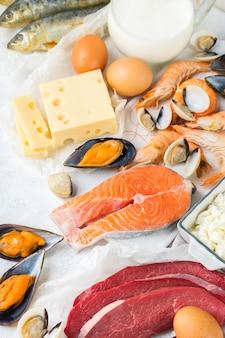 Nutrição de dieta equilibrada, conceito de alimentação saudável. fontes de alimentos ricos em vitamina b12, cobalamina na mesa da cozinha. vista superior do plano de fundo