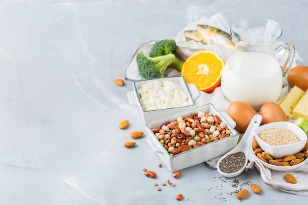 Nutrição de dieta equilibrada, conceito de alimentação saudável. variedade de fontes alimentares ricas em cálcio, feijão, laticínios, sardinhas, brócolis, sementes de chia, amêndoas na mesa da cozinha. copie o fundo do espaço