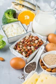Nutrição de dieta equilibrada, conceito de alimentação saudável. variedade de fontes de alimentos ricos em cálcio, feijão, laticínios, sardinhas, brócolis, sementes de chia, amêndoas na mesa da cozinha