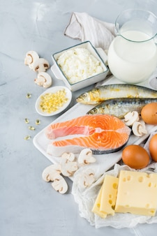 Nutrição de dieta equilibrada, conceito de alimentação saudável. variedade de fontes de alimentos ricos em vitamina d, salmão, laticínios, leite, ovos, queijo, cogumelos, sardinhas na mesa da cozinha
