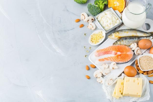 Nutrição de dieta equilibrada, conceito de alimentação saudável. variedade de fontes de alimentos ricos em vitamina de cálcio, salmão, laticínios, sardinhas, brócolis na mesa da cozinha. copie o fundo do espaço
