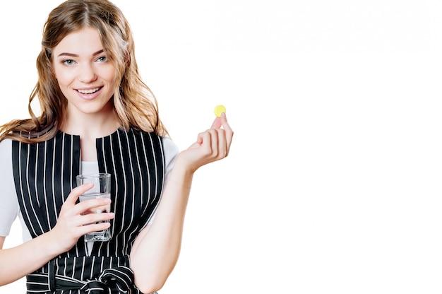Nutrição de dieta saudável. retrato da jovem mulher de sorriso bonita que toma o comprimido da vitamina. close up da menina feliz que guarda o comprimido colorido da cápsula e o copo de água fresca. suplemento dietético. alta resolução