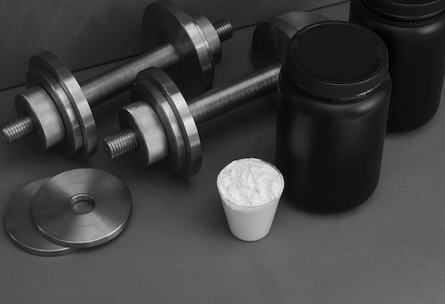 Nutrição esportiva com halteres em uma superfície cinza