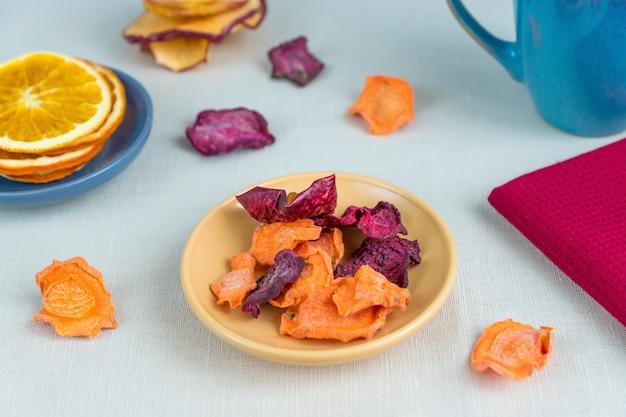 Nutrição orgânica de alimentos saudáveis. maçã fatiada e seca, laranja, cenoura e beterraba e xícara de chá na toalha de mesa têxtil.