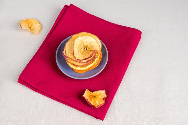 Nutrição orgânica de alimentos saudáveis. maçã fatiada e seca, laranja em fundo de têxteis.