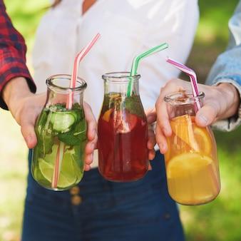 Nutrição saudável. amigos bebendo desintoxicação de suco fresco em fundo verde da natureza. estilo de vida jovem, dieta vegetariana para viagem, comida de fitness, conceito de perda de peso bem-sucedida