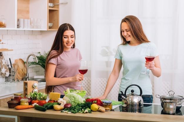 Nutrição saudável. dieta vegetariana. cozinhando. duas mulheres jovens com taças de vinho tinto, olhando para a variedade de alimentos.