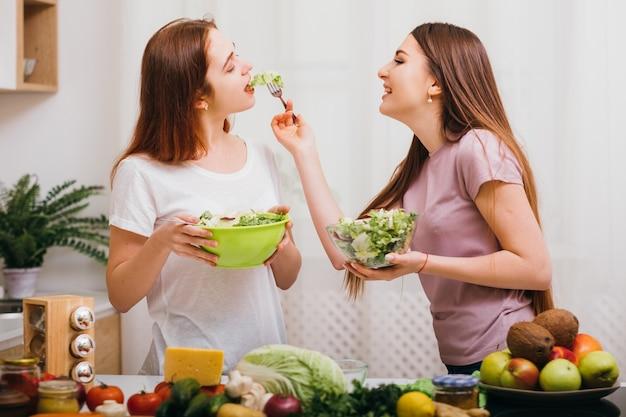 Nutrição saudável. estilo de vida vegano. mulheres jovens com tigelas de salada, alimentando-se mutuamente. variedade de frutas e vegetais.