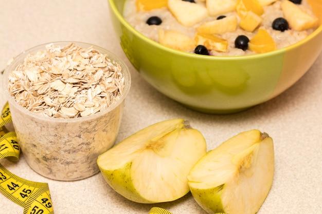 Nutrição saudável pela manhã, quadro de dieta com mingau de aveia, frutas e fita métrica. café da manhã perfeito antes do treino