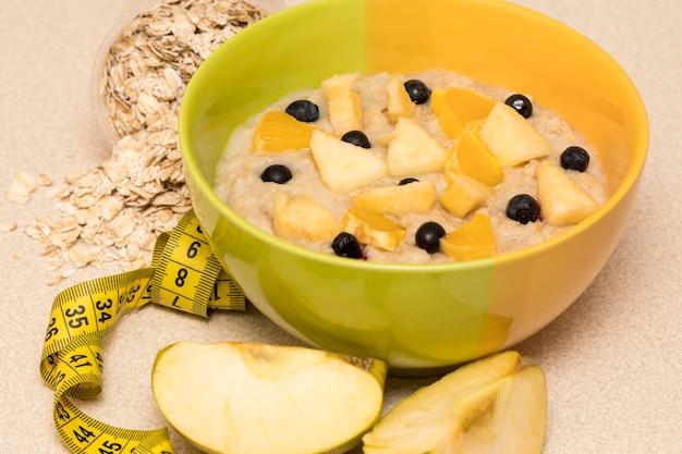 Nutrição saudável pela manhã, quadro de dieta com mingau de aveia, frutas e fita métrica. café da manhã perfeito antes do treino Foto Premium