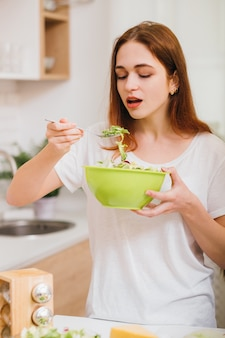 Nutrição vegetariana saudável. hábitos alimentares femininos. mulher jovem e atraente, degustação de salada fresca.