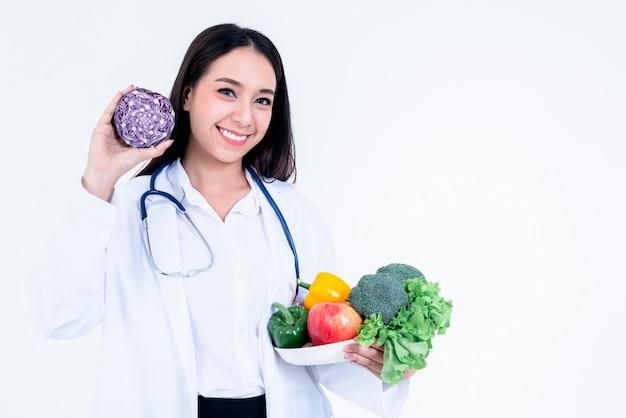 Nutricionista asiática segurando e mostrando muitos legumes frescos e frutas