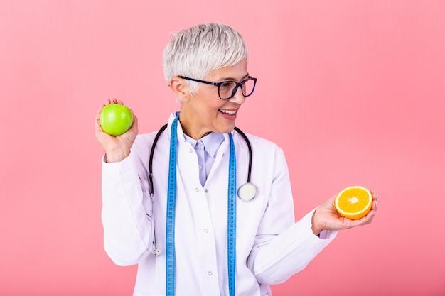 Nutricionista com fruta saudável, suco e fita métrica.