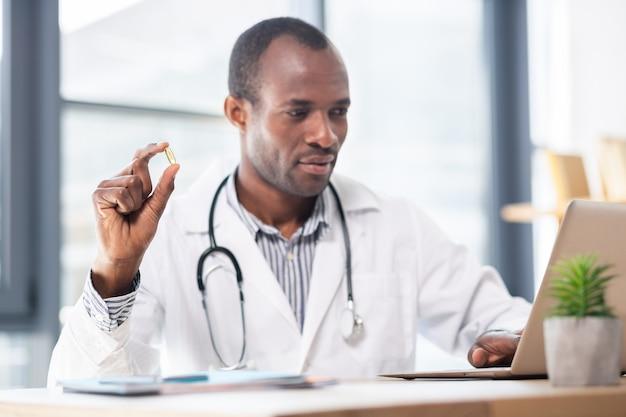 Nutricionista competente sentado em seu local de trabalho e demonstrando vitamina em comprimido