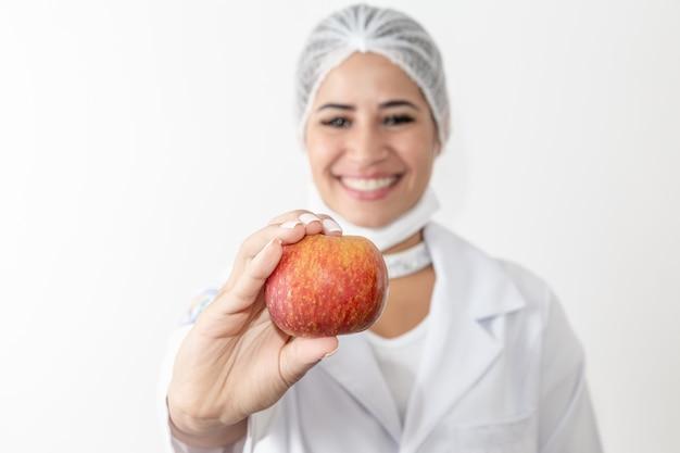 Nutricionista da jovem mulher que guarda uma fruta da maçã. doutor mulher.