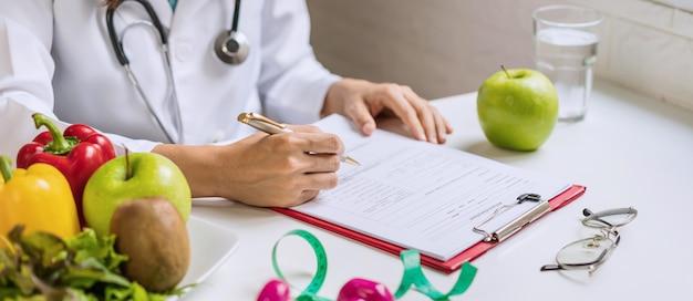 Nutricionista, dando consulta ao paciente com frutas e vegetais saudáveis, nutrição certa e conceito de dieta