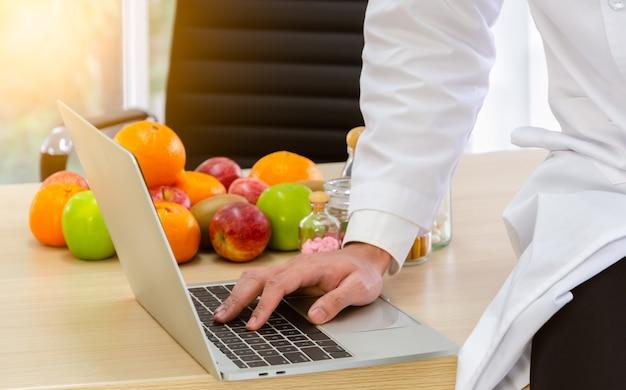 Nutricionista de jaleco branco no trabalho, sentado na mesa de madeira e digitando consulta dietética em um laptop