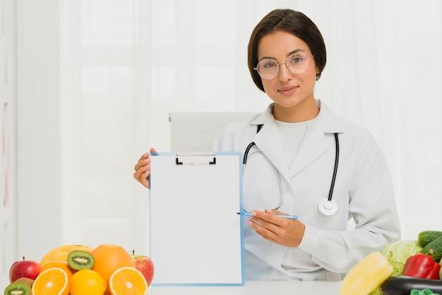 Nutricionista de tiro médio segurando uma prancheta