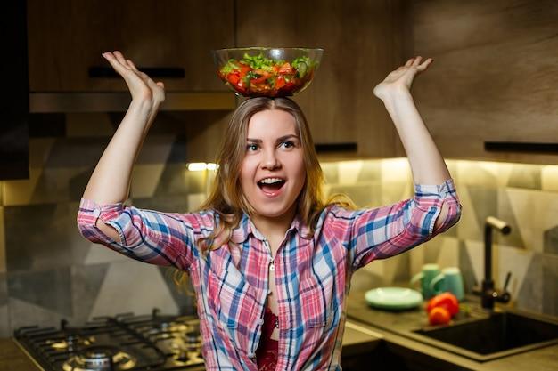 Nutricionista de vegetariano de instrutor de fitness garota preparar salada de legumes fresca na cozinha. assistindo a figura dela