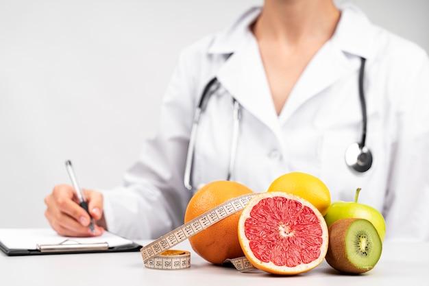Nutricionista escrevendo e lanche de frutas saudáveis