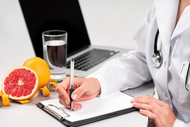 Nutricionista escrevendo em uma prancheta