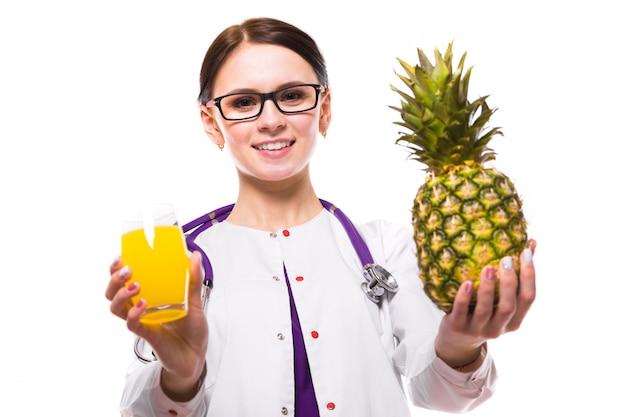 Nutricionista feminina segurar abacaxi e copo de suco fresco nas mãos dela sobre fundo branco