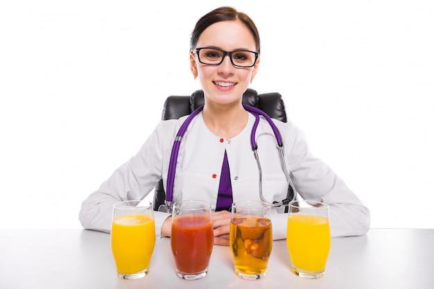 Nutricionista feminina sentada no seu local de trabalho, mostrando e oferecendo copo de suco de tomate de maçã e abacaxi laranja