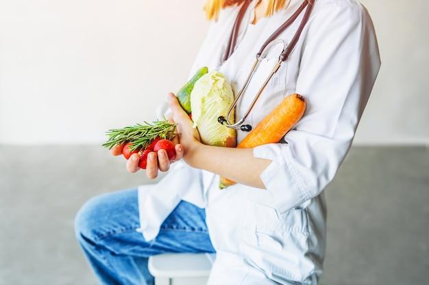Nutricionista médica holbing alimentos saudáveis nas mãos.