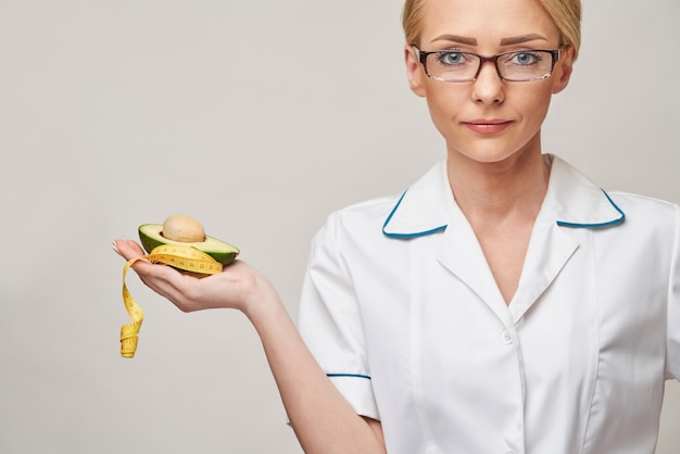 Nutricionista médico conceito de estilo de vida saudável - segurando abacate orgânico e fita métrica