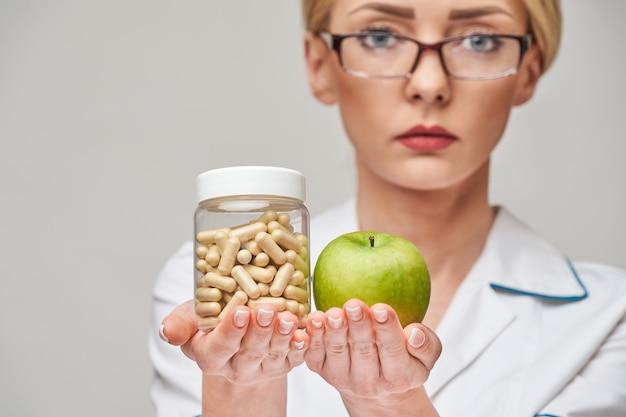 Nutricionista médico conceito de estilo de vida saudável - segurando cápsulas de maçã verde fresca orgânica e lata de vitaminas