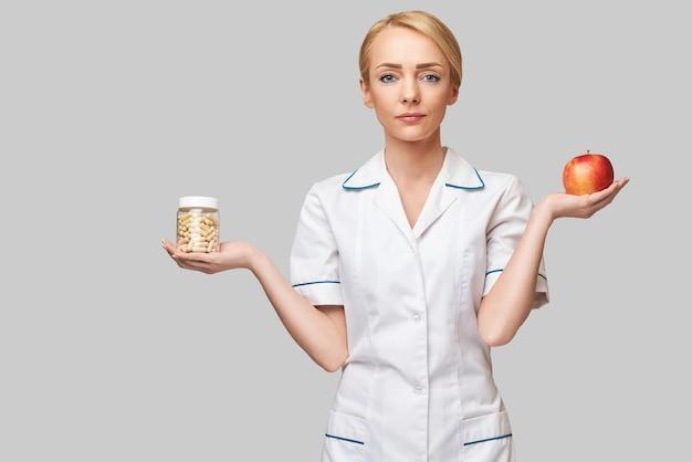 Nutricionista médico conceito de estilo de vida saudável - segurando pílulas de maçã vermelha orgânica e vitaminas ou medicamentos