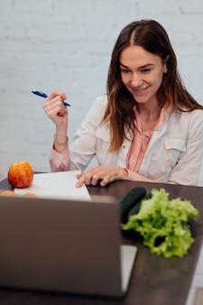Nutricionista médico consulta online. uma médica se senta em sua mesa na frente de seu laptop e fala em uma chamada de vídeo.
