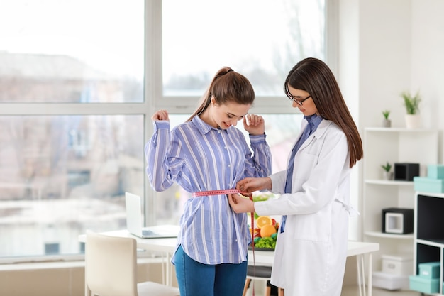 Nutricionista medindo a cintura de uma jovem em uma clínica de perda de peso