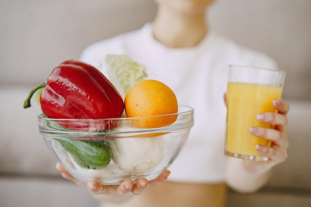Nutricionista mostrando suco e tigela de legumes