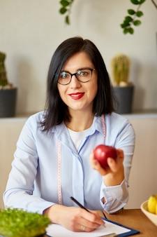 Nutricionista, nutricionista no escritório, segura a maçã na mão, frutas e vegetais saudáveis, conceito de saúde e dieta. nutricionista feminina com frutas trabalhando em sua mesa.