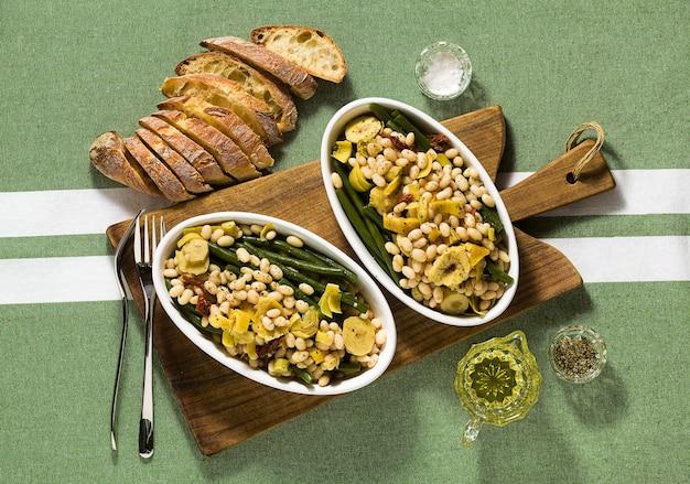 Nutritiva salada de feijão branco cannellini com feijão verde, tomate seco e alcachofra em óleo.