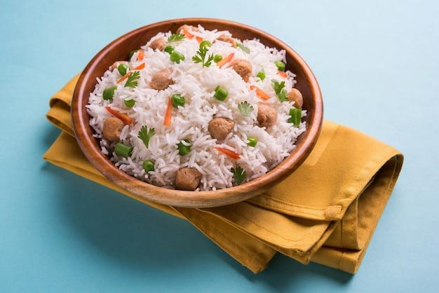 Nutritivo pulao de soja ou pilaf ou pedaço de soja arroz frito com ervilha e feijão. servido em uma tigela sobre fundo colorido ou de madeira. foco seletivo
