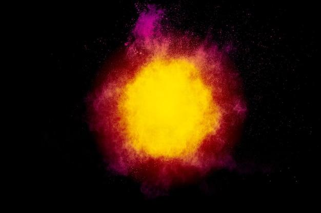 Nuvem de explosão de pó amarelo vermelho sobre fundo preto. congele o movimento de salpicos de partículas de poeira de cor amarelo-vermelho.