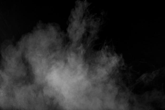 Nuvem de explosão de pó branco contra fundo preto. respingo de partículas de pó branco.
