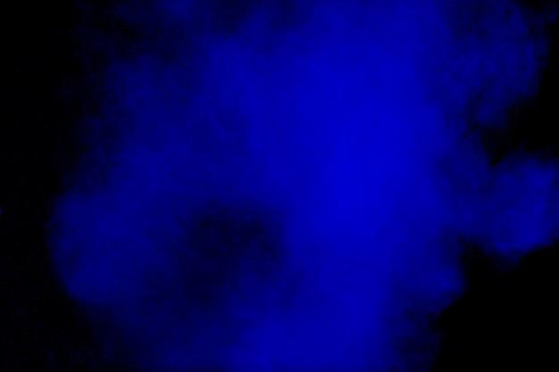 Nuvem de explosão de pó de cor azul no preto