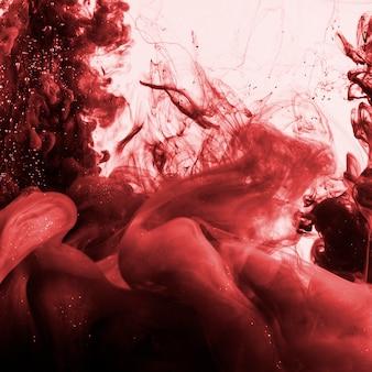 Nuvem de fumaça vermelha densa escura no líquido