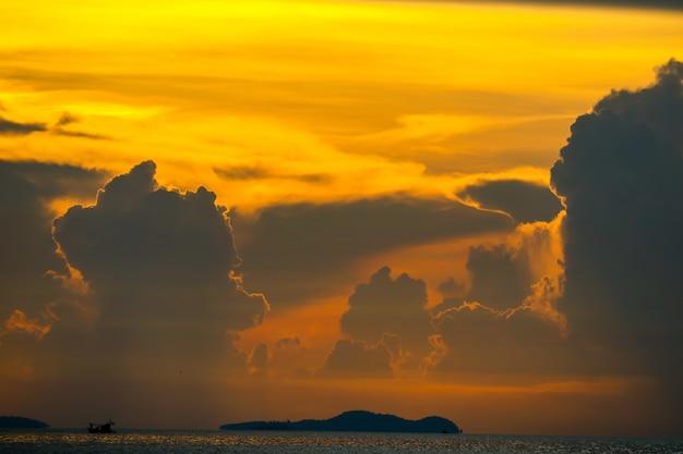 Nuvem do por do sol no barco de pesca do céu da silhueta no mar e na ilha