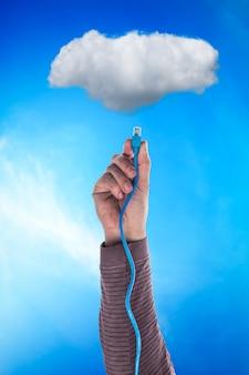 Nuvem e mão com cabo sobre azul