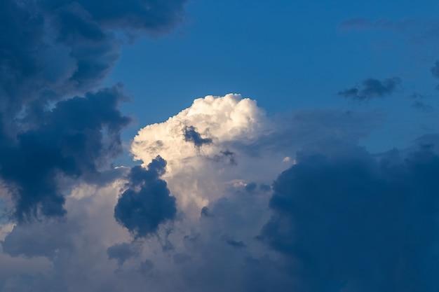 Nuvem encaracolada branca e rosa cercada por nuvens de tempestade escuras