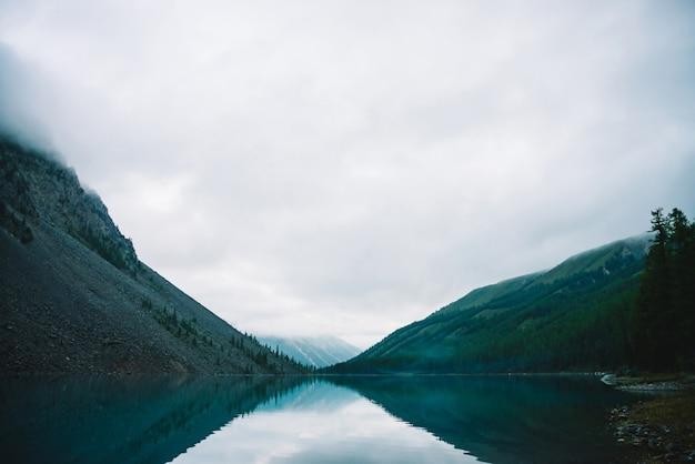 Nuvem gigante acima da montanha rochosa com as árvores no nevoeiro. lago de montanha incrível. cordilheira sob céu nublado. rochas maravilhosas na névoa. paisagem de manhã da natureza das montanhas. nuvens baixas nas montanhas.