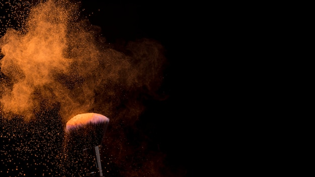 Nuvem laranja de pó e pincel de maquiagem em fundo escuro