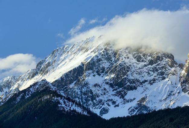 Nuvem no pico da rocha do inverno e floresta na encosta (áustria).
