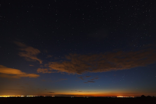 Nuvens à noite de estrelas brilhantes no céu após o pôr do sol.