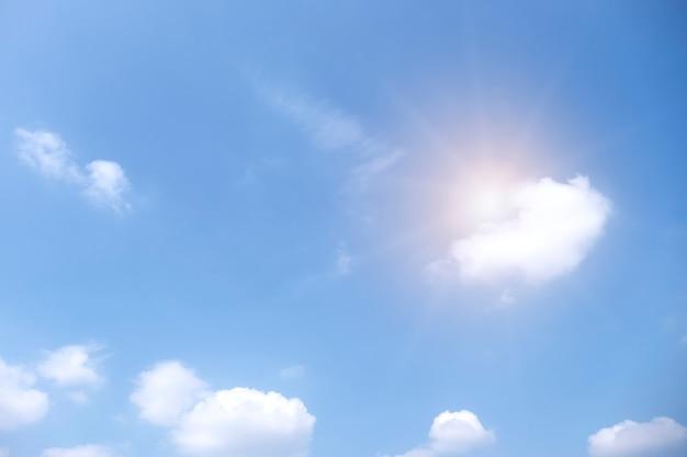 Nuvens brancas bonitas com o sol no céu azul.