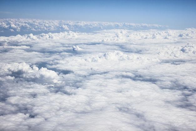 Nuvens brancas / cinzentas pesadas na vista de um avião, com céu azul e luz do sol, um avião está voando acima das nuvens